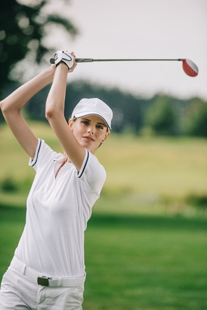portrait of female golf player in cap with golf club in hands at golf course