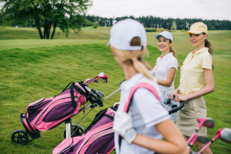 selective focus of smiling women in caps with golf equipment on golf course