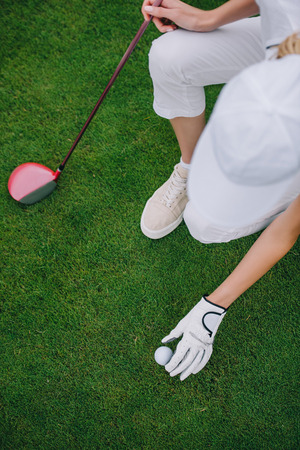 overhead view of woman in cap and golf glove putting ball on green lawn at golf course Stok Fotoğraf