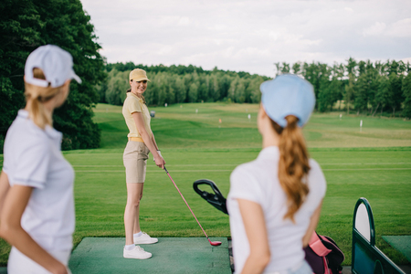 selective focus of smiling female golf player looking at friends at golf course