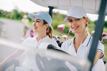 portrait of smiling female golfers in caps riding golf cart at golf course Stok Fotoğraf