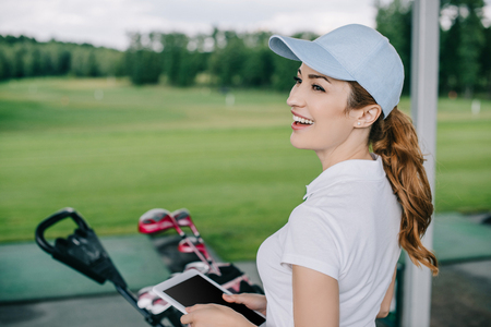 side view of cheerful female golf player with tablet in hands at golf course