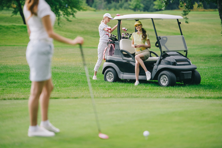 selective focus of woman with golf club and friends resting at golf cart on green lawn Stok Fotoğraf