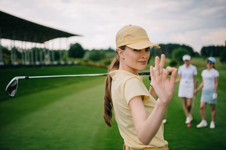 selective focus of female golf player with golf club showing ok sign at golf course