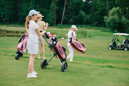 selective focus of women with golf gear walking on green lawn at golf course Stok Fotoğraf