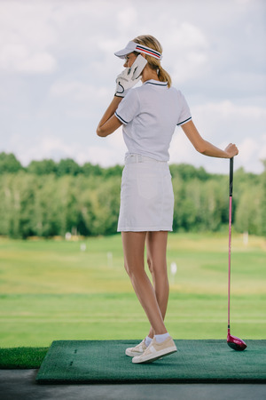 side view of female golf player in polo and cap with golf club in hand talking on smartphone at golf course