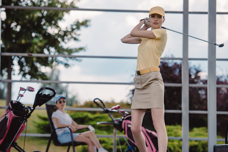 selective focus of female golf player playing golf while friend resting behind at golf course