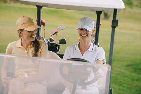 smiling female golf players riding golf cart at golf course Stok Fotoğraf - 109046661