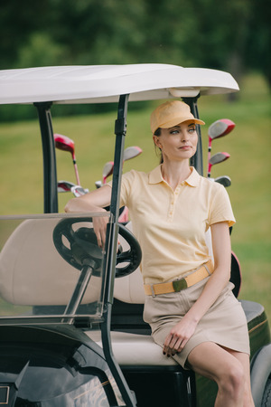 portrait of smiling woman in polo and cap sitting on golf cart and looking away