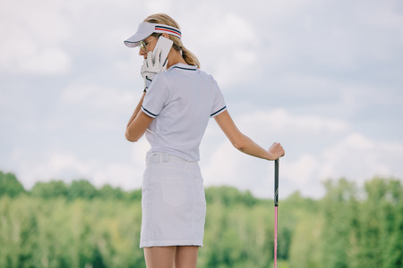 side view of female golf player in polo and cap with golf club in hand talking on smartphone at golf course Stok Fotoğraf - 109046678