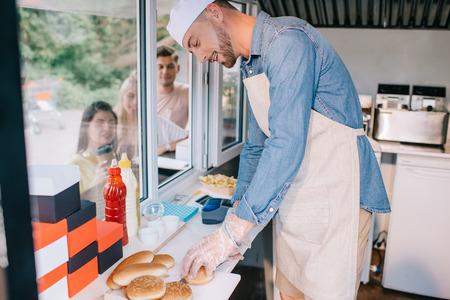 lachende jonge chef-kok die in een foodtruck werkt terwijl jonge mensen in de buurt staan Stockfoto