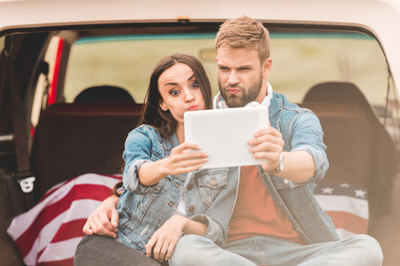 beautiful young couple making selfie with tablet while sitting in car trunk during trip