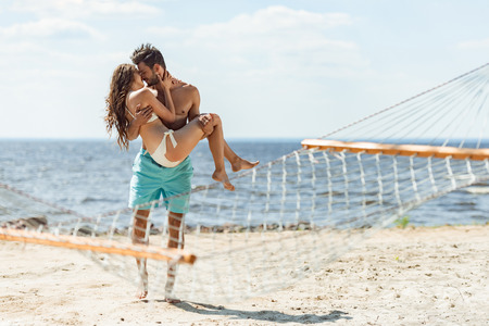 man holding girlfriend on hands and kissing her on beach, with hammock on foreground