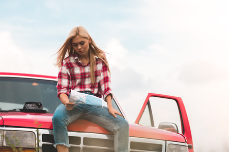 beautiful young woman sitting on car and looking at map