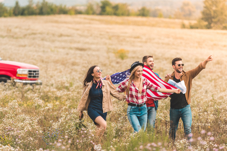 group of young american travellers with flag walking by flower field and pointing somewhere