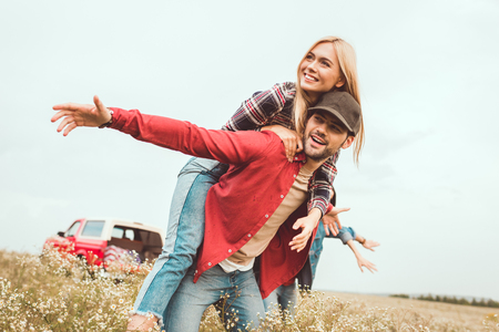smiling young woman piggybacking on boyfriend in flower field with blurred car on background