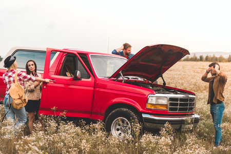 group of young car travellers having trouble with engine and stuck in field
