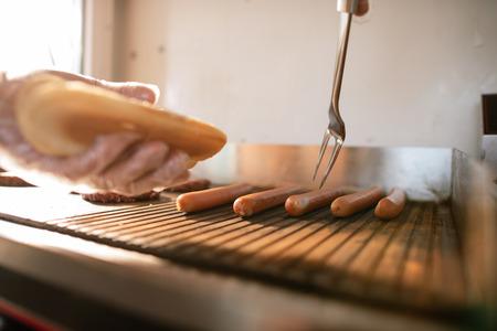Imagen recortada del chef preparando perro hod en camión de comida y tomando salchichas
