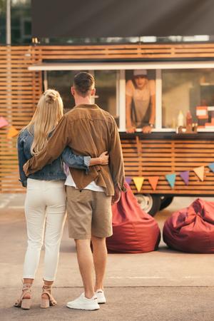 vista posteriore di una coppia in piedi vicino a un camion di cibo