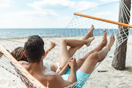 couple of tourists relaxing in hammock on beach near the sea Stock Photo