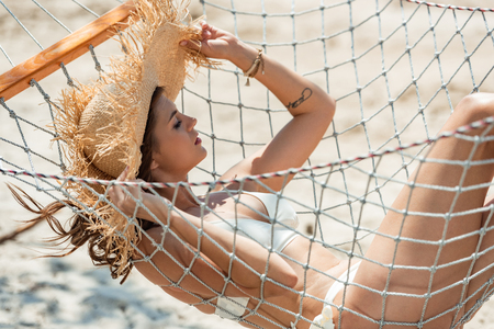 attractive girl in swimsuit and straw hat resting in hammock on beach