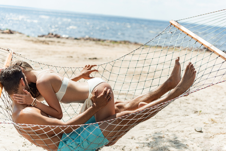couple of lovers kissing and resting in hammock on beach near the sea Stok Fotoğraf