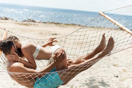 paar geliefden zoenen en rusten in een hangmat op het strand in de buurt van de zee