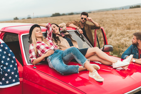 group of american car travellers relaxing in flower field