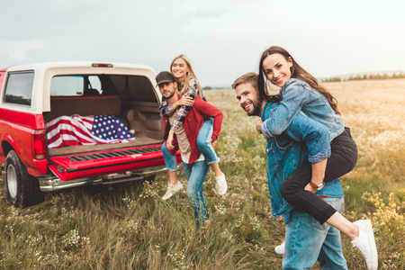 young happy women piggybacking on boyfriends in flower field during car trip Stock Photo