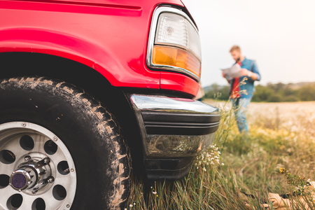 close-up shot of red truck standing in field with blurred man navigating with map on background