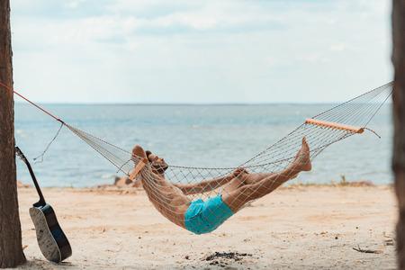 handsome bearded man lying in hammock on beach near the sea