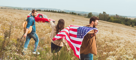 group of friends with united states flag in flower field during car trip Stock Photo