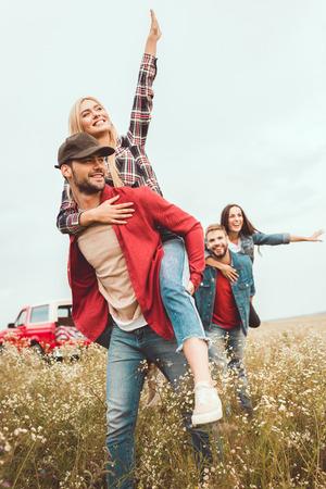 young women piggybacking on boyfriends in flower field Stock Photo