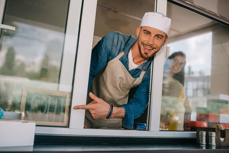 cheerful young man smiling at camera and pointing with finger at sign open in food truck