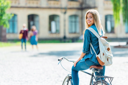 Selective focus smiling young student with backpack on bicycle looking at camera on street Stock fotó - 109068695