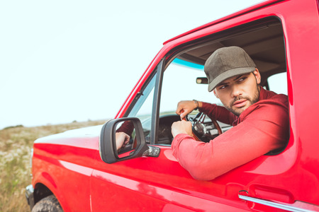 Handsome young man driving old red truck in field and looking back