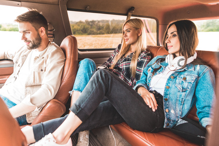 Happy group of friends sitting in car while having trip Standard-Bild