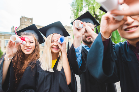 Selektiver Fokus multikultureller Absolventen mit Diplomen im Park
