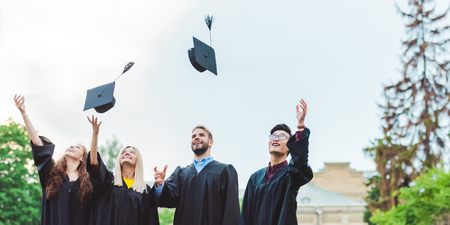 Portrait of happy multicultural graduates throwing caps up in park Stock Photo