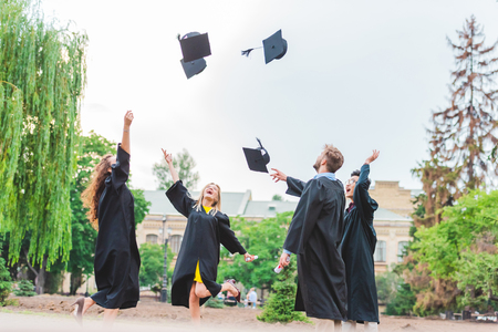 Happy multicultural graduates with diplomas throwing caps up in park Stock Photo