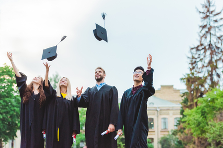 Portrait of happy multicultural graduates with diplomas throwing caps up in park Stock Photo