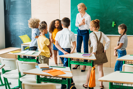 Group of classmates standing around teacher at classroom