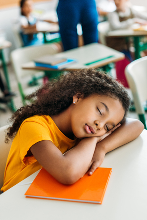 Tired African american schoolgirl sleeping on desk during lesson Stock Photo