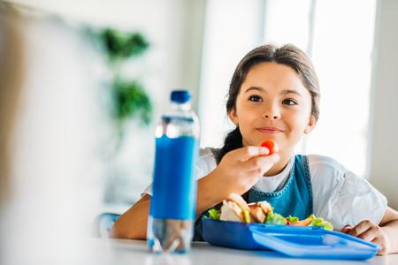 Happy little schoolgirl eating lunch at school cafeteria