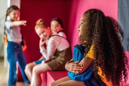 Schoolgirls bullying on their African american classmate at school