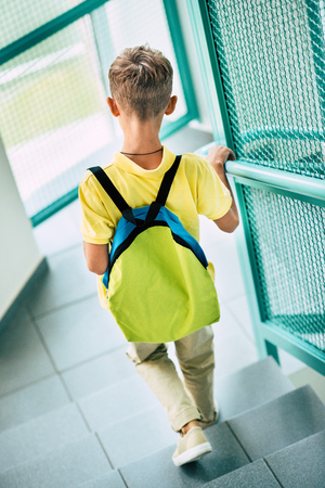 Rear view of schoolboy with backpack going downstairs at school corridor
