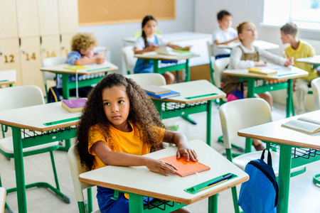 Beautiful bored African american schoolgirl sitting on lesson with classmates blurred on background