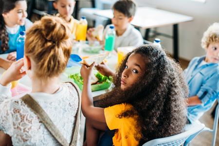 African american schoolgirl taking lunch at school cafeteria with her classmates and looking at camera 写真素材