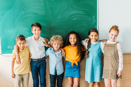 Group of multiethnic schoolchildren embracing in front of blank chalkboard