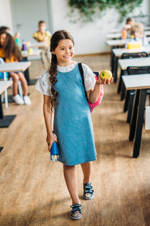 happy little schoolgirl with apple and bottle of water at school cafeteria 写真素材